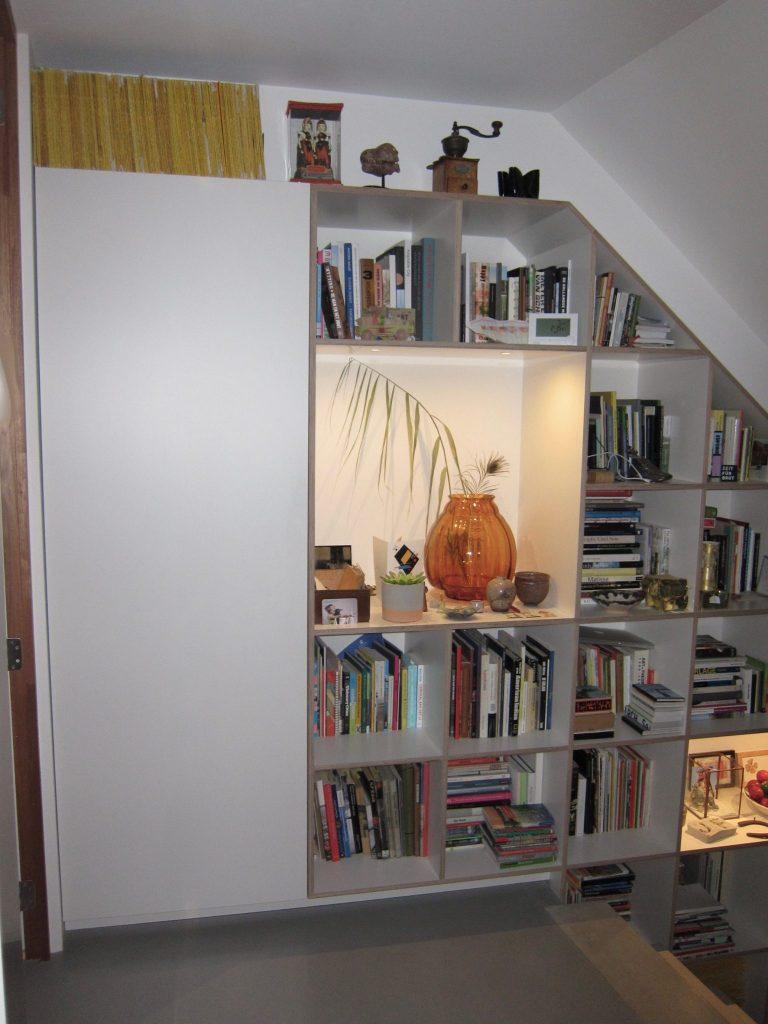 Bovenaan de trap verdwijnt een gedeelte van de kast achter een greeploze deur